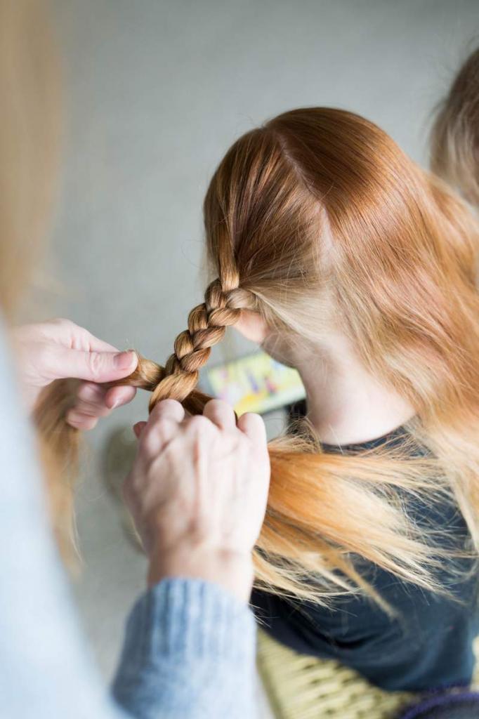 девочке плетут косичку